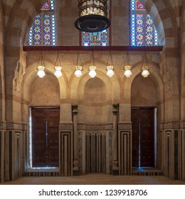 Cairo, Egypt - November 3 2018: Marble wall with mihrab (niche), two wooden doors, huge arches and stained glass windows at mosque attached to Khayer Bek Mausoleum, Darb Al-Ahmar district
