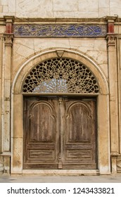 Cairo, Egypt - November 8, 2018: Old wooden door and vintage wall with two old windows located in Saladin's castle with some blue text above and red ornament above columns