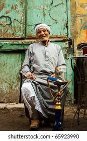 Cairo, Egypt - October 11, 2010: Friendly old Egyptian man wearing a long gray robe, a jellabiya, sitting, laughing at graffiti wall outdoor street cafe smoking sheesha water pipe in Islamic Cairo