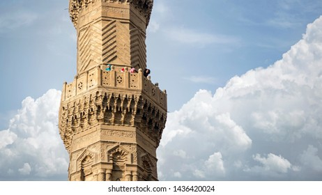 CAIRO, EGYPT OCTOBER 12, 2018: The medieval Bab Zuweila gate located in the heart of Islamic Cairo and surrounded by a noisy Arab market. People on top of one of the towers are watching the city.