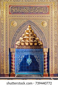 Cairo, Egypt - October 21, 2017: Golden ornate arched mihrab (niche) with floral pattern, blue Turkish ceramic tiles and arabic calligraphy, Mosque of The Manial Palace of Prince Mohammed Ali Tewfik