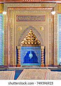 Cairo, Egypt - October 21, 2017: Golden ornate arched mihrab (niche) with floral pattern, blue Turkish ceramic tiles and arabic calligraphy at the public mosque of Manial Palace of Prince Mohammed Ali