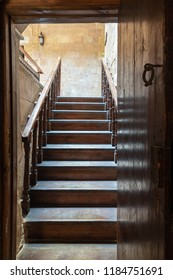 Cairo, Egypt - September 15 2018: House of Egyptian Architecture historical building. Open wooden door revealing wooden old staircase going up with with reflections of the stairs on the door