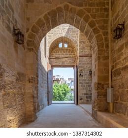 Cairo, Egypt- September 22 2018: Passage at Al-Muayyad Bimaristan (hospital) historic building with stone bricks wall, stone arches, and entrance door, Darb Al Labana district, Old Cairo