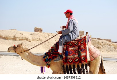 Cairo / Giza, Egypt - May 7, 2008 - Camel rider in the desert of Sahara. Bedouin and camel near the Pyramids.