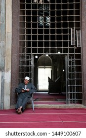 Cairo,Egypt - 06-01-2019: Older man reading from the koran in front of iron gate in the sultan hassan mosque egypt. Man in mosque reading, islamic religion background. Historic, muslim culture