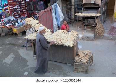 Cairo,Egypt.09.10.2018.Egyptian vendor offering traditional flat bread or aish baladi for sale in the street.