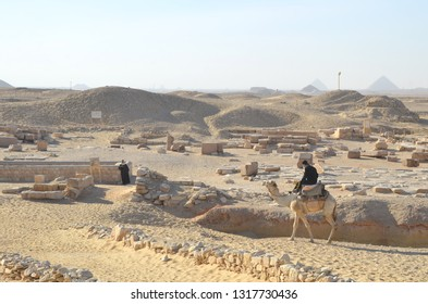 Cairo/Egypt_18 Feb 2019: A man riding his camel crossing the dunes of Cairo. A desert land nearby Djoser Step Pyramid.