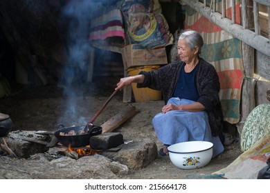 CAJAMARCA , PERU -  CIRCA 2014: Portrait of an unidentified woman while cooking with firewood, circa 2014 in Cajamarca, Peru.