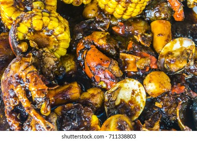 Cajun food with corn and crabs and black pepper sauce