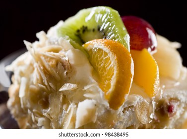 Cake with almonds and fruits on the dark background