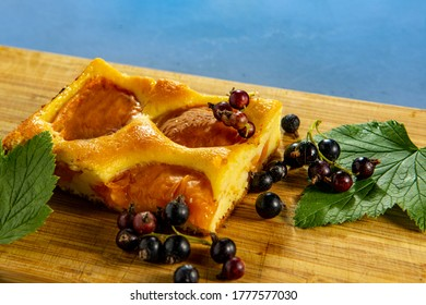 Cake with apricot and blackcurrant decorated with currant leaves on a wooden board