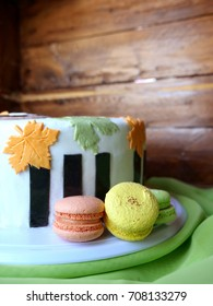 Cake with autumn leaves and macaroons on a wooden boards  background. Multicolored macaroons.