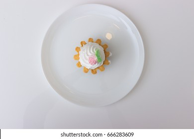 cake basket with cream on a plate isolated on white table. Top view.