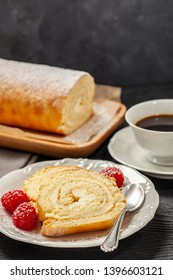 Cake - biscuit roll with mascarpone cream on a saucer, next to coffee in a cup, all placed on a black wooden counter