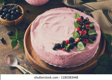 Cake with Black Currant Cream Souffle and Biscuit on a table in a rustic style. Toned image.
