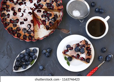 A cake with blackthorns berries is located on a dark background. A piece of cake on a separate plate. In the photo there is a cup of coffee and a vase with berries of the blackthorn.
