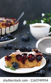 A cake with blackthorns berries is located on a dark background. A piece of cake in the foreground. In the photo there is a cup of coffee and a vase with berries of the blackthorn.