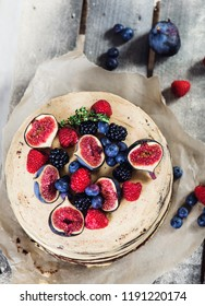 Cake with buttercream frosting decorated with figs and berries shot from top