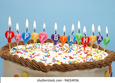 A cake and it's candles that read happy birthday.