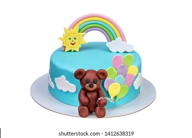 Cake for a children's holiday with a bear balls and a rainbow.