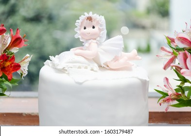 Cake for christening girl. Decorated with a doll and flowers