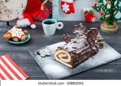 Cake Christmas log on New Year's table on the wooden background