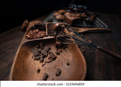 cake cooking table with hot chocolat stick on the mixer and a lot of dark chocolat in a wooden tray.
