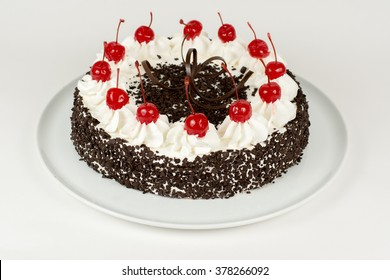 Cake with cream on plate isolated on light background
