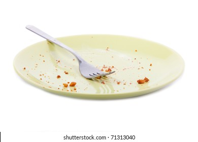 Cake crumbs and fork on yellow plate isolated on white background