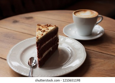 Cake and cup of coffee on a wooden desk table
