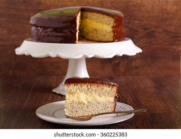 Cake with custard cream and chocolate glaze over on dark wooden background