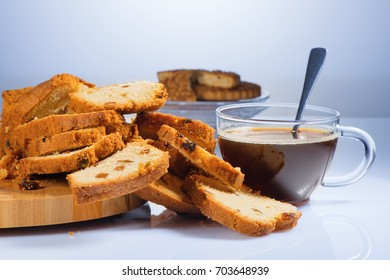 The cake cut on pieces with raisin on a beautiful chopping board and black coffee in a glass cup