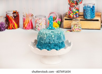 A cake decorated in blue has a number one candle to celebrate that one year mark. First birthday smash the cake.