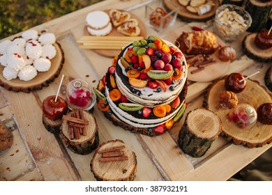 cake decorated with flowers, berries and fruits on a wooden table decorated with logs, caramel apples, sweets and macaroon