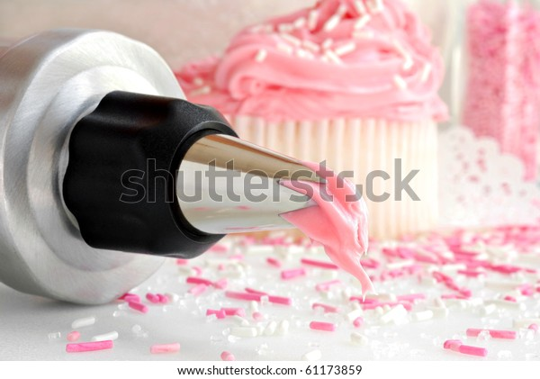 Cake decorating still life with fresh strawberry frosting dripping from pastry tip and cupcakes with sprinkles in background.  Macro with shallow dof.