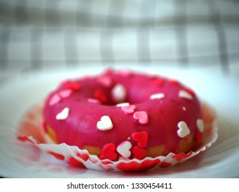 Cake donut with white, pink and red hearts on a plate