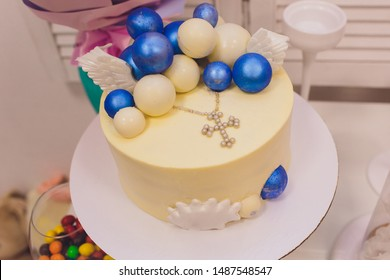 Cake for the first holy communion with cross on white background.