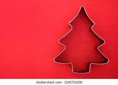 Cake forms for Christmas baking on a bright red background. Tin form for gingerbread cookies. There's room for text. Form baking christmas tree.