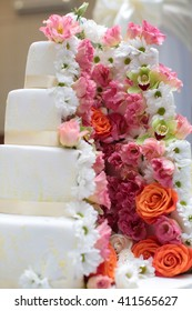 Cake four-layer beautiful traditional anniversary birthday wedding delicious sweet dessert decorated with butter-cream roses flowers on blurred background