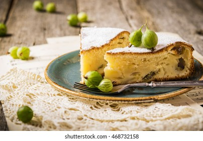 Cake with fresh berries. Light summer cake, pie with gooseberries on wooden rustic background with lacy napkin. Summer desserts and pastries. Selective focus