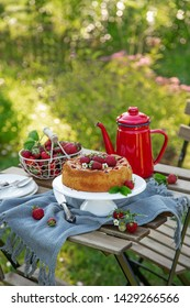 cake with fresh strawberry on wooden table in a garden, outdoor, selective focus