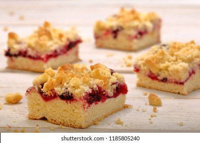 Cake with fruit and crumble on white wooden background