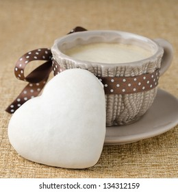 cake with icing in the form of heart and a cup of coffee closeup