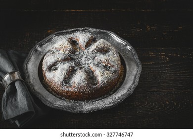 Cake with icing sugar with napkin in the vintage metal ring
