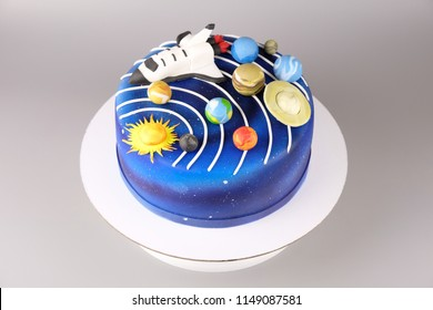 Cake with the image of the cosmos drawn by airbrush. Galaxy, stars, solar system with planets and spaceship. Picture for a menu or a confectionery catalog.