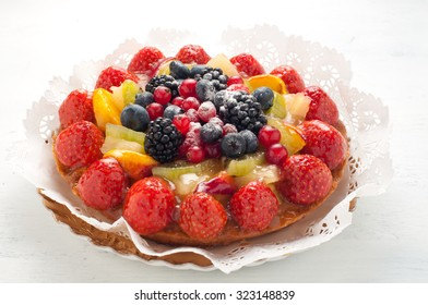 Cake with lots of fresh fruit : strawberries , kiwi , melon , berries