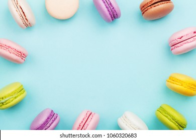 Cake macaron or macaroon on turquoise pastel background from above. Colorful cookies on dessert top view.