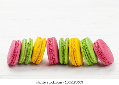 Cake macaron or macaroon sweets on wooden backdrop. With copy space