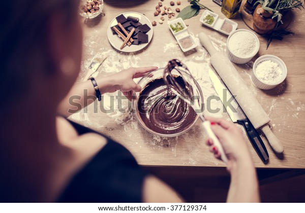 Cake making, preparation.Preparations for making homemade chocolate.Mixed ingredients prepared for baking cake or bake.A whisk in a round bowl with liquid chocolate.Housewife making a chocolate cake